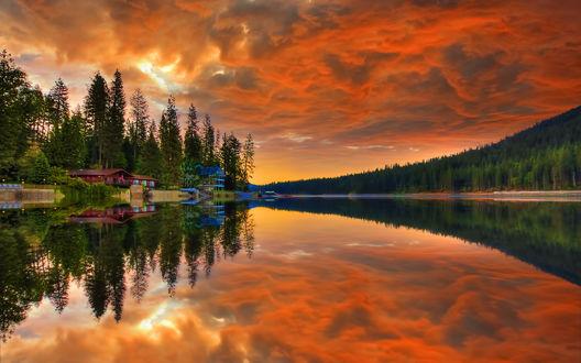 Обои Небольшие домики, стоящие на берегу широкой реки на фоне красивого заката неба, отражающегося в водной глади, высокими елями, растущими по берегам