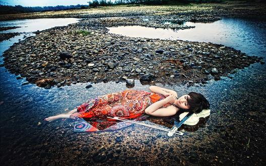 Обои Девушка восточной внешности лежит в воде у каменистого берега, положив голову на белую скрипку