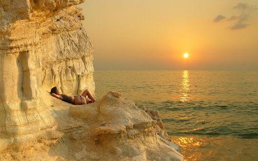 Обои Девушка, встречающая утренний восход солнца, лежащая на скальной гряде необычной расцветки, находящейся у морского берега