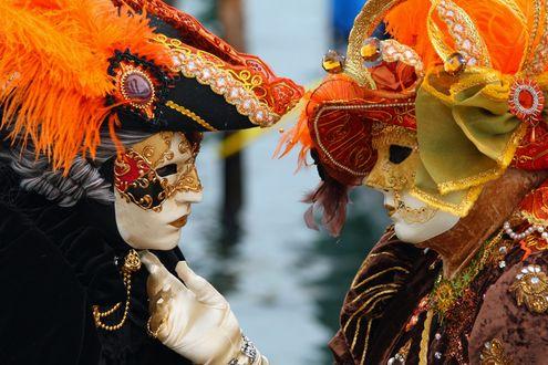 Обои Два человека в масках, одетые в карнавальные костюмы, стоят напротив друг друга на фоне воды