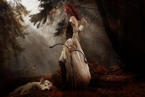 Обои Рыжая девушка с луком в руках стоит в лесу рядом с застреленным, ее же стрелой, волком