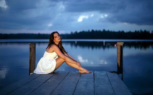 Обои Девушка в коротком белом платье сидит на мостике на фоне озера, над которым спускаются сумерки