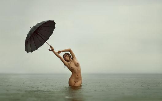 Обои Обнаженная девушка в дождливую погоду стоит с черным зонтом в море