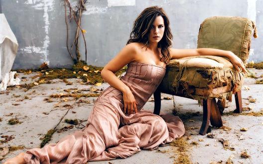 Обои Актриса Kate Beckinsale / Кейт Бэкинсейл сидит на бетонном полу среди желтых осенних листьев, облокотившись о старое кресло