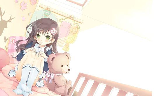 Обои Девочка сидит на кровате рядом с плюшевым медведем