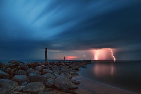 Обои Разряды молнии на небе с грозовыми облаками над каменистым морским побережьем, фотография Tamara Patrejeva