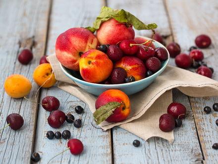 Обои На деревянном столе стоит чашка с нектаринам и ягодами черешни и черной смородины, рядом лежат абрикосы, ягоды черной смородины и черешни