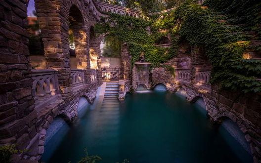 Обои Красивый бассейн с уходящей вглубь воды каменной лестницей, обнесенный вокруг каменной стеной с оригинальным орнаментом, обросшей зеленью. фотография Arkhipow Dmitriy