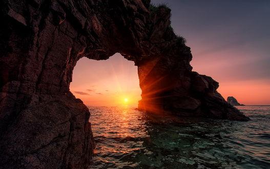Обои Яркие лучи заходящего за линию горизонта солнца, осветили естественную арку, образованную в скале. расположенной на морском побережье, фотография Arkhipow Dmitriy