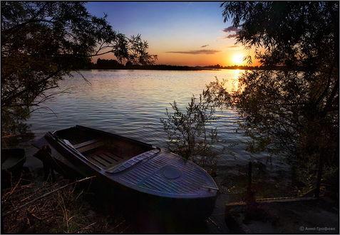 Обои Лучи заходящего за линию горизонта вечернего солнца высветили световую дорожку на озере, на берегу, рядом с деревьями стоит металлическая рыбацкая лодка, фотография Анны Графовой