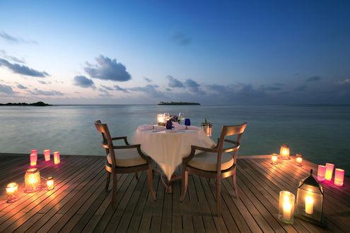 Обои Стол, накрытый на двоих на пристани у моря среди ламп со свечами