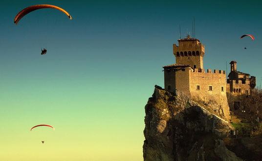 Обои Парашютисты парят в безоблачном небе цвета лазури, пролетая над старинной каменной крепостью, стоящей на горном утесе, фотография Krasi Matorov