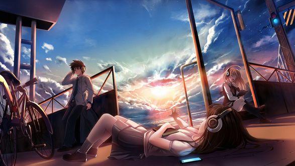 Обои Девушка в школьной форме, в наушниках с книгой в руке, лежит на дороге протягивая руку, рядом стоит парень в наушниках и девушка