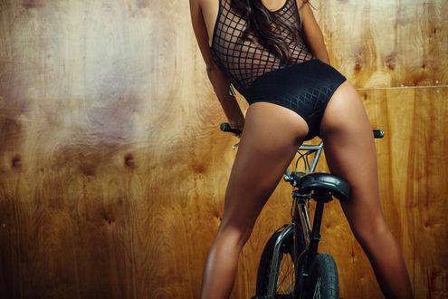 Обои Модель Jeannie Santiago / Джинни Сантьяго в черном боди на велосипеде у коричневой стены