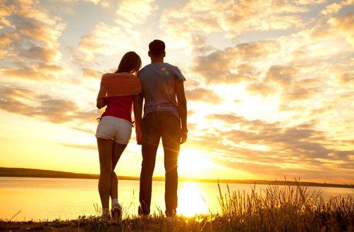 Обои Влюбленная пара любуется солнечной дорожкой на водной глади реки, и красками облаков в лучах заходящего солнца