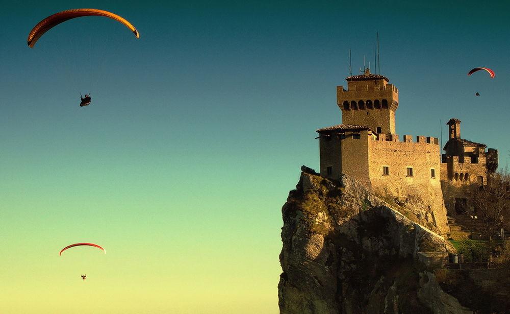 Обои для рабочего стола Парашютисты парят в безоблачном небе цвета лазури, пролетая над старинной каменной крепостью, стоящей на горном утесе, фотография Krasi Matorov