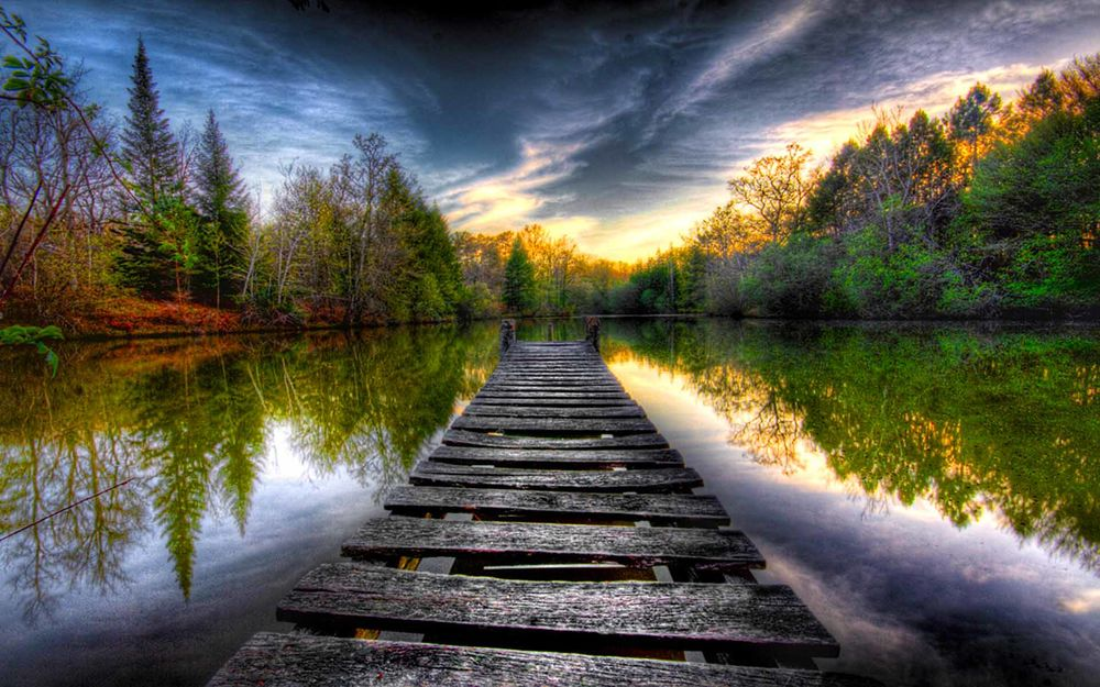 Обои для рабочего стола Деревянный пирс на озере, по берегам которого растут деревья, небо и природа отражаются в воде