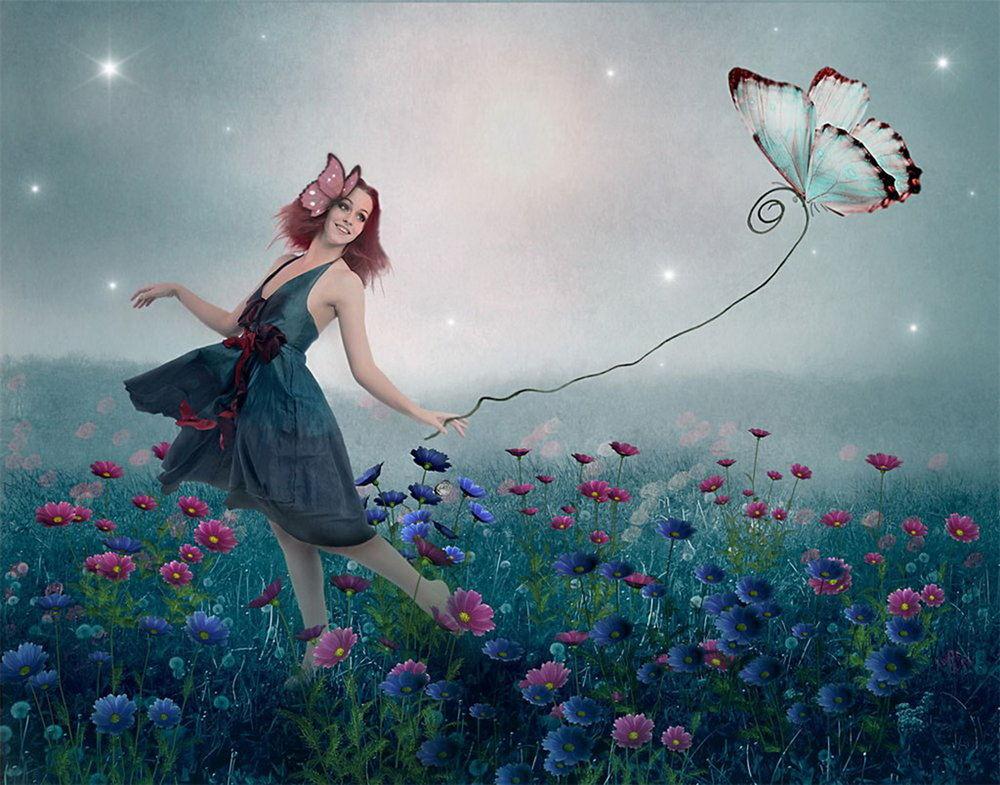 Обои для рабочего стола Улыбающаяся рыжеволосая девушка с заколкой-бабочкой в волосах, идущая по полю с разноцветными герберами, держащая в руке веревку с привязанной к ней бабочкой на фоне звездного неба, покрытого туманной дымкой, фотография Nataliorion