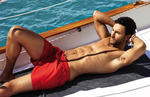 Обои Актер Ноа Миллс / Noah Mills в красных шортах лежит на палубе яхты
