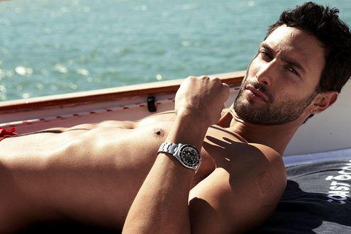 Обои Актер Ноа Миллс / Noah Mills с голым торсом и часами на руке лежит на палубе яхты