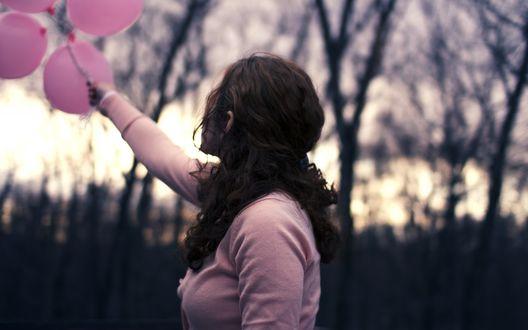 Обои Девушка держит в руке связку розовых воздушных шаров на фоне голых осенних деревьев