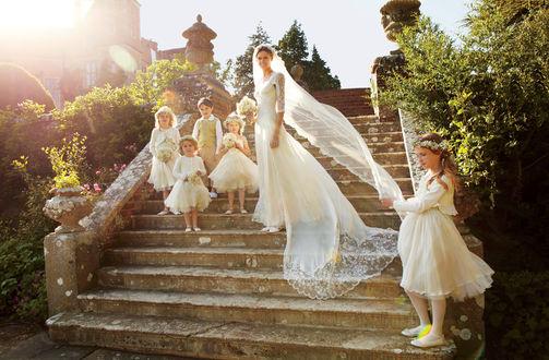 Обои Британская модель Жакетта Уиллер / Jacquetta Wheeler стоит в свадебном платье на каменных ступенях в окружении детей