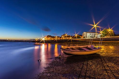 Обои Прогулочная многоместная лодка, стоящая на якоре на берегу морской бухты, усыпанным галькой и рядом стоящие каменные дома с ярко горящим наружным электрическим освещением на фоне ярко-синего неба, фотография Paulo Mendonca
