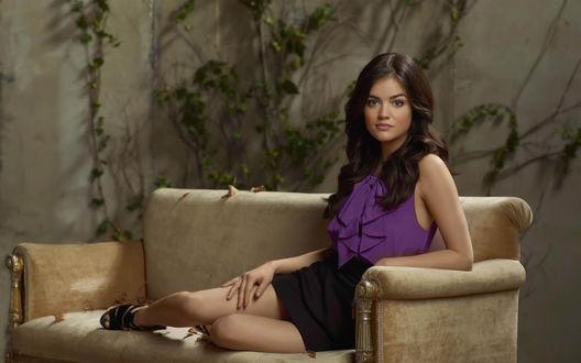 Обои Актриса Люси Хейл / Lucy Hale сидит на диване в комнате, где стены обвиты плющом