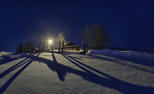 Обои Небольшой деревянный домик с ярко светящимися окнами, огороженный деревянной изгородью, окруженный деревьями и ярко горящим уличным фонарем на фоне звездного ночного неба и созвездия Большая Медведица, фотография optimist