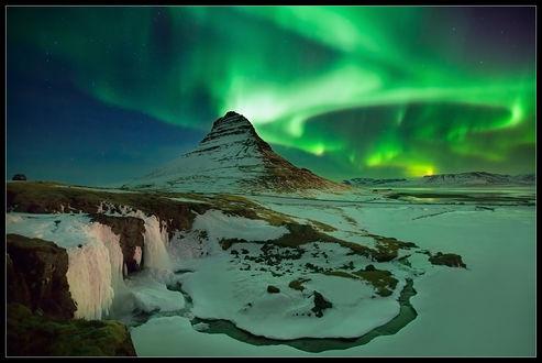Обои Занесенная снегом гора, окруженная замерзшим водоемом, покрытом снежным покровом на фоне ночного неба и красивого Северного сияния, Исландия / Iceland, фотография Виктора Рогатнева