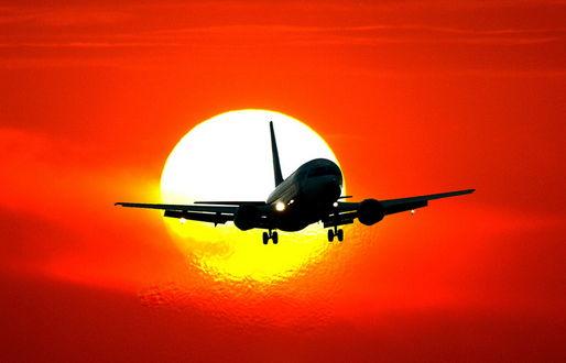 Обои Пассажирский самолет с включенными бортовыми фарами, заходящий на посадку на фоне ярко светящегося солнечного диска и багряного заката, фотография балаганофф