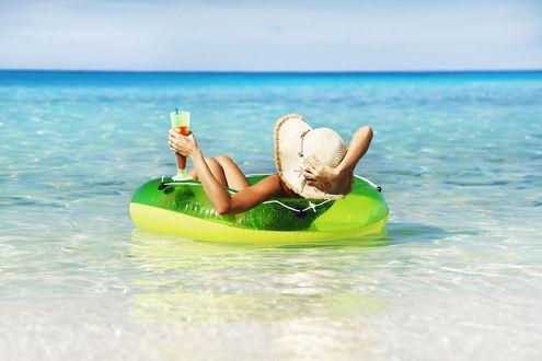 Обои Девушка расслабляется на надувном круге в море с коктейлем в руке