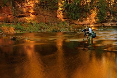 Обои Белокурая женщина фотограф, одетая в защитный комбинезон, стоящая в воде, освещенной золотистыми солнечными лучами, настраивает свой фотоаппарат, стоящий на треноге в воде, фотография Olegs Petrejevs