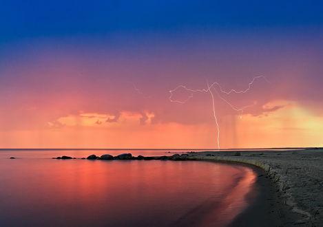 Обои Красивая, необычная молния в многослойном небе, состоящим из синего, фиолетового и желтого оттенков облаков над озером, водная поверхность которого озарена фиолетовым свечением, фотография Olegs Petrejevs
