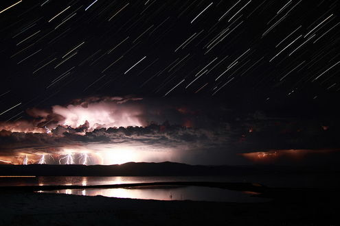 Обои Молнии, сверкающие между небом и поверхностью гор и необычные красивые звездные треки в ночном, грозовом небе над озером Байкал, Россия / Baikal, Russia, фотография Sirano