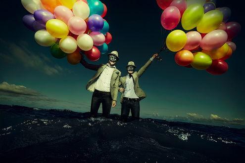 Обои Двое мужчин в шляпах и масках, стоящие по колено в морской воде держат в руках большое количество разноцветных, надувных воздушных шариков, фотография Козин Ждет четвертого Всадника