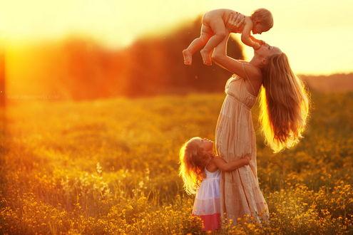 Обои Стройная, длинноволосая молодая женщина, одетая в длинное белое платье, находящаяся в поле среди одуванчиков, подбрасывает на руках вверх своего голого сыны, возле ног, обхватив мать за подол платья стоит ее дочка, на фоне ярких солнечных лучей полуденного солнца, фотография Ирины Ремпель
