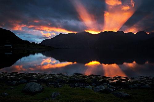 Обои Лучи восходящего из-за гор утреннего солнца как прожектором осветили небо с темными облаками, отразившись в темной водной глади горного озера, фотография Andrey Bondarev