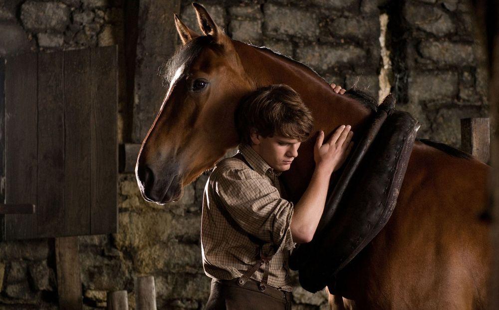 Обои для рабочего стола Кадр из фильма Боевой конь / War Horse - Джереми Ирвин / Jeremy Irvine в роли Альберта / Albert обнимает коня Джоуи / Joey