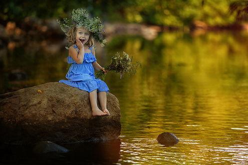 Обои Милая, светловолосая, улыбающаяся девочка в синем легком сарафане с венком на голове из полевых цветов, держащая в руке такой же небольшой букетик, сидящая на большом валуне на водоеме, фотография Натальи Законовой