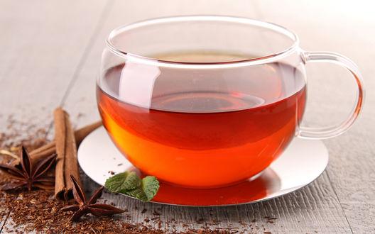 Обои Чашка чая, стоящая на блюдце, рядом с кружкой палочки корицы и бадьян, на блюдце лежат листья мяты