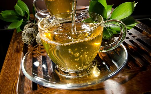 Обои Кружка ароматного чая, стоящая на блюдце с зелеными листочками
