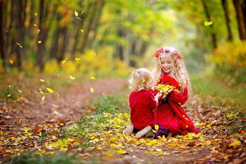 Обои Белокурые брат и сестра, одетые в красную одежду, стоящие на коленях на лесной дорожке, усыпанной осенними листьями, держащие в руках, сплетенных вместе, горсточку таких же листьев, фотография Светланы Квашниной