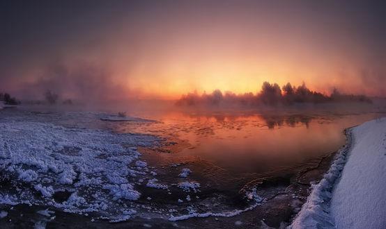 Обои Утреннее восходящее солнце над рекой, покрытой у берегов снежной крошкой и покрывающееся тонким слоем льда русло реки морозным утром, легким туманом, парящим над еще не замерзшей водой, фотография Алексея Угальникова