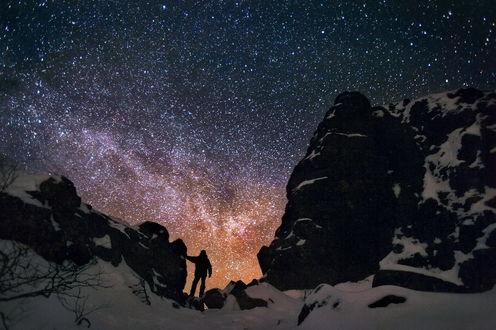 Обои Силуэт мужчины, стоящего среди заснеженных скал и любующегося ночным звездным небом с Млечным путем, фотография Бродяга с севера