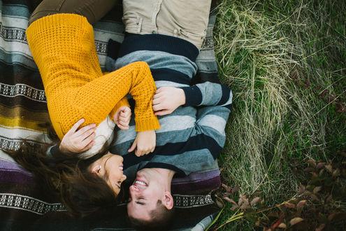 Обои Девушка в оранжевом свитере лежит на покрывале на траве с мужчиной и улыбается