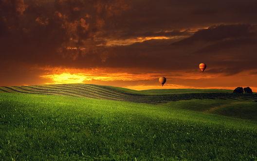 Обои Воздушные шары, летящие в небе над зелеными полями, расположенными на холмистой местности на фоне красивого заката, фотография Антона Шваина