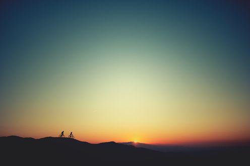 Обои Двое людей едут по горам на велосипедах при закате солнца