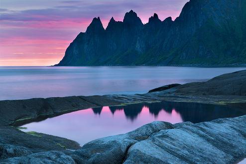 Обои Восходящее утреннее солнце осветило своими лучами розовые облака над гористым морским побережьем, отразившимися на водной поверхности небольшого водоема среди каменистого берега, автор Андрей