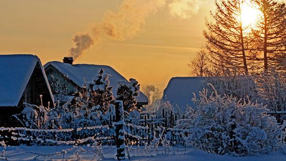 Обои Восходящее утреннее солнце осветило своими яркими лучами деревянные домики, огороженные забором из деревянного штакетника, клубящимся над одной из крыш белым дымом из печной трубы, ветки кустов и деревьев покрыты густым слоем снега